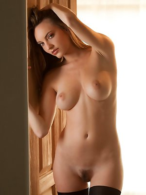 removes her top in a dim, sunlit room